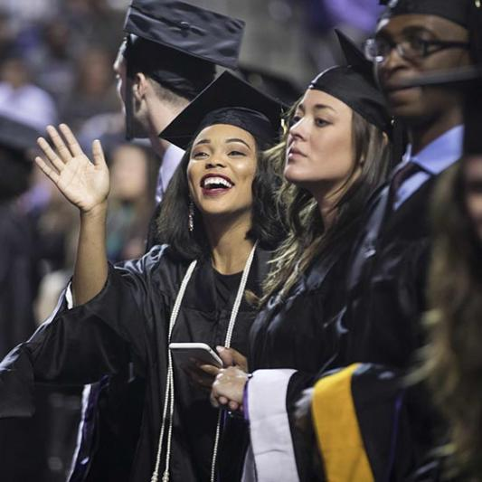 Graduates waving to family on commencement day