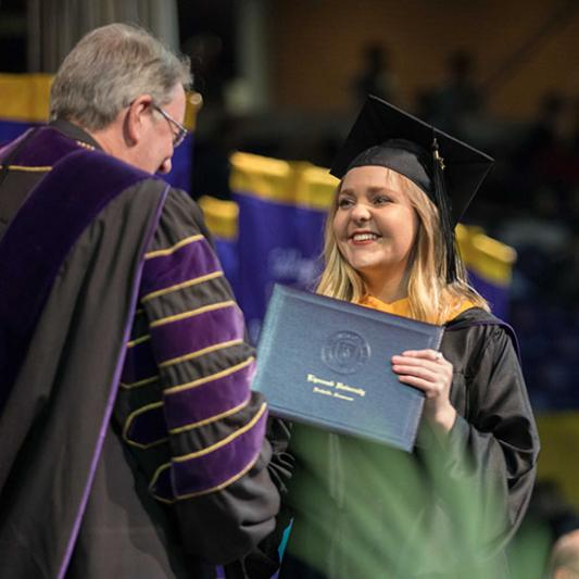 A student receives her diploma