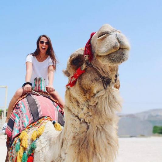 student rides a camel in Israel