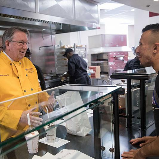 President Lowry serves at the opening of Creekstone Burgers