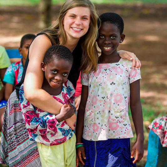 Student stands with two children while on a mission trip