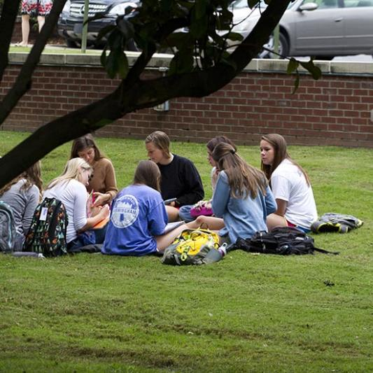 Students sit outside in the grass during a Breakout Chapel session