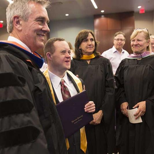 IDEAL students stand beside their professors in graduation robes.