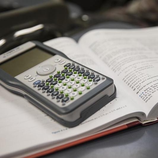 Calculator sits on top of a mathematics textbook.