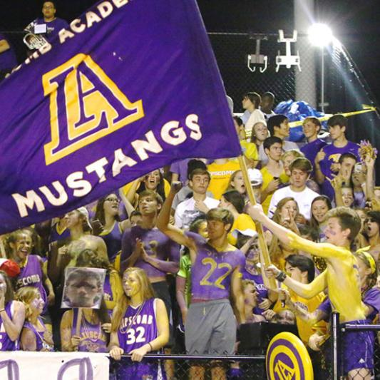 A crowd of Lipscomb Academy students cheer on their athletes with an LA Mustangs flag and gear, body paint