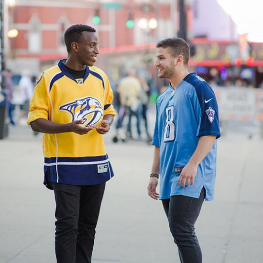 A student in a Nashville Predators hockey jersey talks with another in a Tennessee Titans football jersey.
