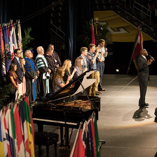 Students, faculty, staff and guests sing together during Convocation in Allen Arena.