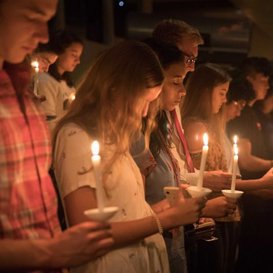 Students pray together with illuminated candles during Initium.
