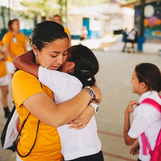 A Lipscomb student on mission and a young student hug in El Salvador.