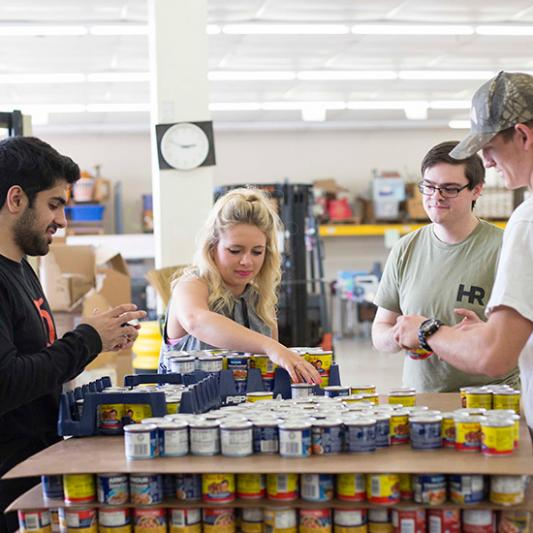 Four students work together sorting cans in a food bank for Service Day.