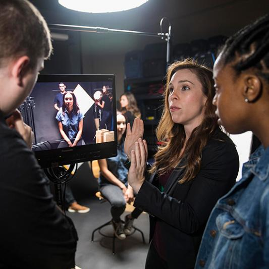 Several students on a set working with a video camera and lighting