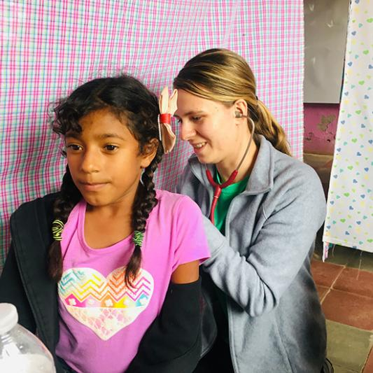 A student health professional helps a local in Honduras.