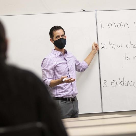 A professor teaches a class wearing a face mask to help minimize virus transmission risks.