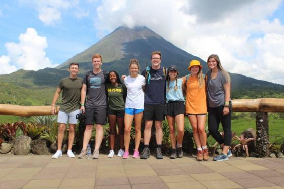 Students standing in front of a volcano.