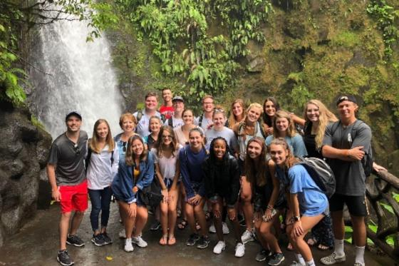 Group of students standing at waterfall