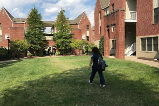 Student walking in front of dorms.