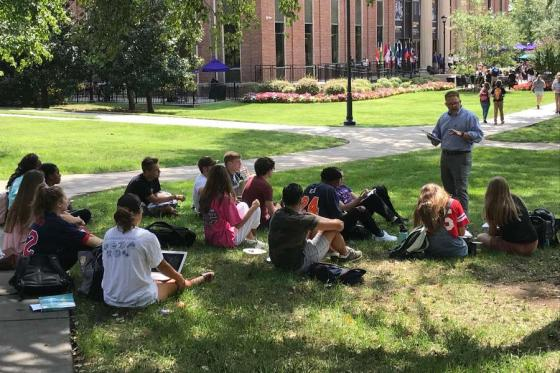 Group of students sitting under tree listening to faculty member.