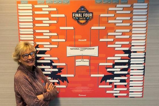 Diane Turnham standing next to NCAA women's basketball tournament brackets