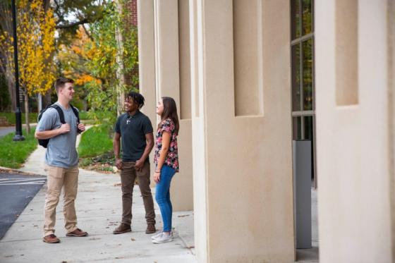 Three students standing in front of a building on the Lipscomb campus.