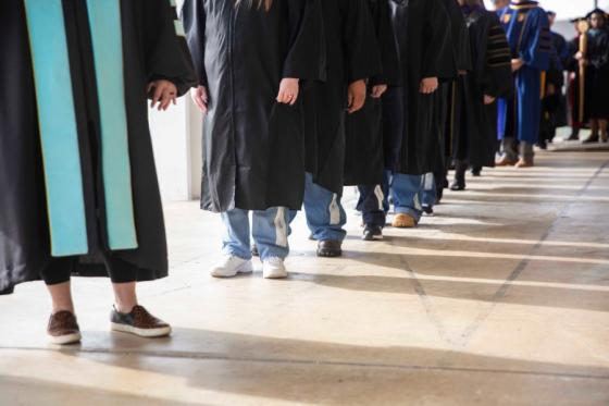 Graduates wearing graduation robes over prison blues.