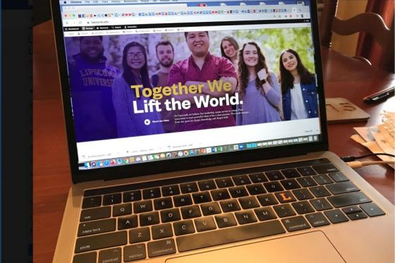 A laptop in a home showing the Lipscomb University home page