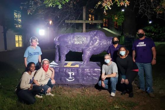 Graduate students sitting around Bison on campus