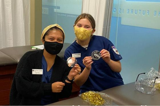 Photo of two nursing students wearing masks and buttons