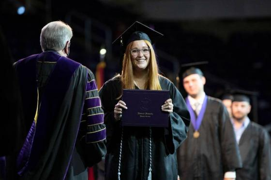 Smiling student crosses the stage with diploma