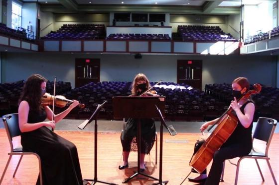 Student music trio performing to an empty auditorium with masks on