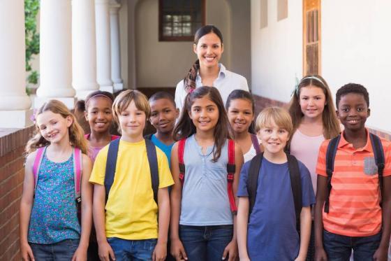 Group of children standing with an elementary school teacher.