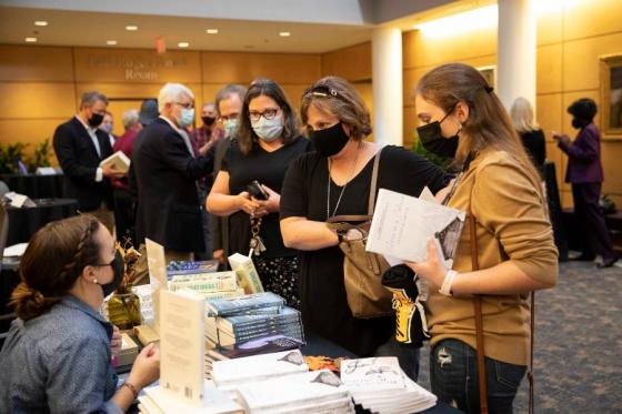 Guests at the faculty signing event purchase books.