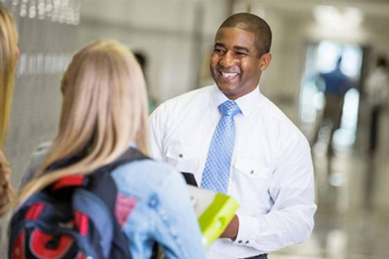 Principal in hallway talking to teacher